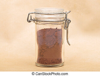 Cacao powder in jar with lid on brown background