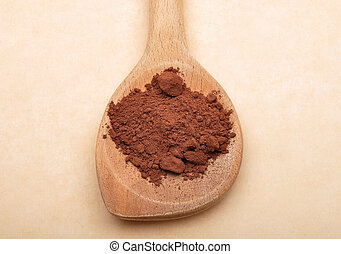 Cacao powder on wooden spoon on brown background
