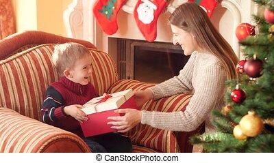 cadeau, vidéo, salle, mère, donner, séance, année, noël, famille, jeune, vivant, elle, fauteuil, fils, réception, arbre., suivant, 4k, peu, nouveau, beau