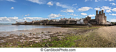 Caernarfon Castle and town as seen from the beach. All...