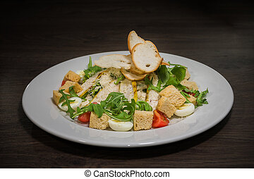 Caesar salad in a white plate on a wooden background