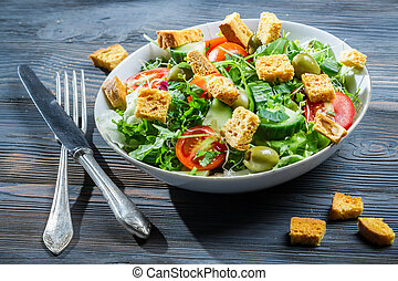Caesar salad made of fresh vegetables on old table
