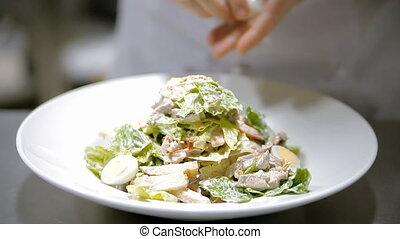 Caesar salad on a plate - A cook is preparing Caesar salad....
