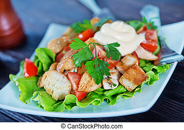 caesar salad on white plate and on a table