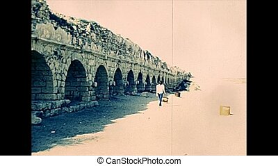 Roman aqueduct of Caesarea town located in Caesarea National Parkby the sea, built by Herod king. Historical archival footage in the 1970s of Israeli national park.