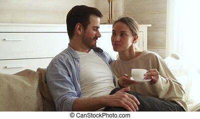 café, séance, thé, couple parler, embrasser, boire, sofa, heureux