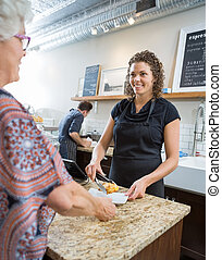 Cafe Owner Serving Sweet Food To Senior Woman - Smiling...