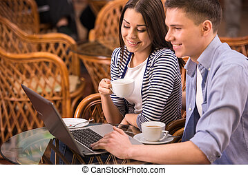 Cafe - Young smiling couple are using laptop at cafe.