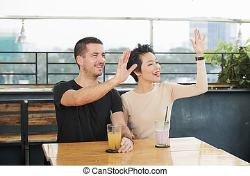 Cafe visitors waving with hands