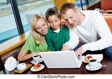 Parents and their male kid using the cafe wi-fi to surf the internet