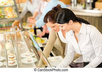 Cafeteria lunch two office woman choose food - Cafeteria...