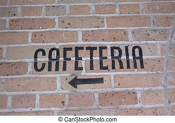 The word cafeteria painted on a brick wall in black paint.
