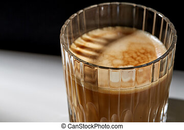 close up of coffee in glass on table