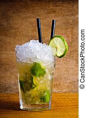 Caipirinha cocktail on a vintage wooden background