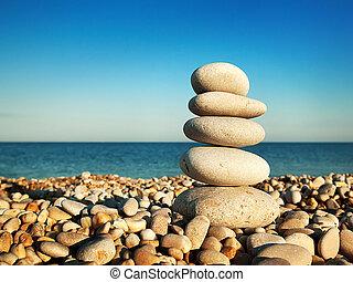 Cairn on the pebbly sea beach against the sky