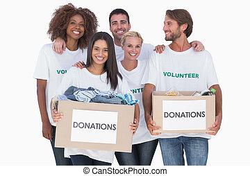 caixas, doação, voluntários, segurando, grupo, roupas, feliz