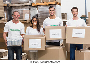 cajas, cámara, donaciones, tenencia, sonriente, voluntarios