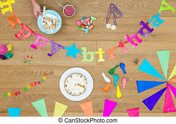 Cake And Birthday Decorations On Wooden Table