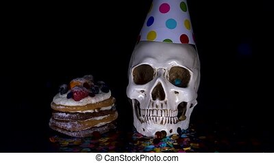 cake and skull in a festive cap on a black background. 4k,...