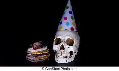 cake and skull in a festive cap on a black background. candy, slow-motion shooting. 4k