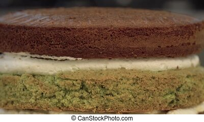 Cake. Brownie. Sweets. Close-up of butter cream on the confection. White gentle cream on a chocolate cake. Close up: delicate cream in a pastry bag. Pastry cream cake is decorated. Sponge cake.