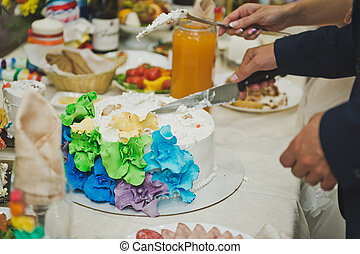 Rainbow wedding cake with flower patterns.