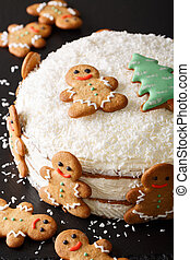 cake is decorated with gingerbread and coconut close-up. vertical