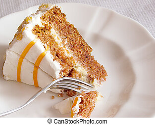 cake on a plate - carrot cake being cut into with a fork