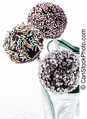cake pop with coloured sprinkles in a glass