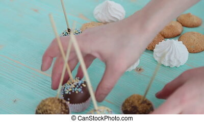 Cake pops and biscuit on wooden table