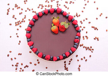 Cake souffle, covered with chocolate, jewelry, berries, raspberry, blueberry, blueberry, strawberry, white background.