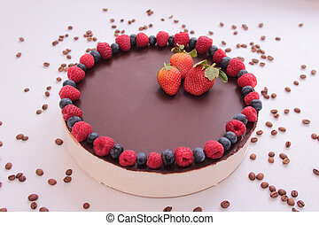 Cake souffle, covered with chocolate, jewelry, berries, raspberry, blueberry, blueberry, strawberry, white background