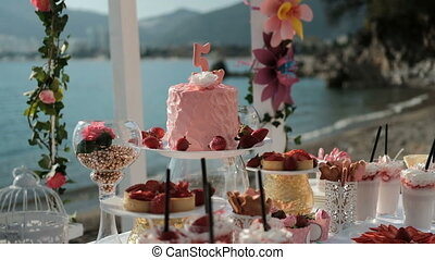 Cake, sweet dishes and flower compositions on table by sea.