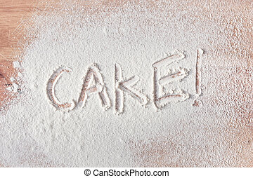 Cake text - Cake written in flour on a wooden surface