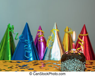 Cake with a candle and colorful caps