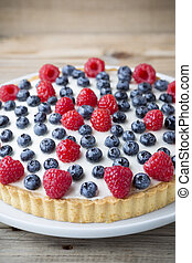Cake with blueberries and raspberries. Confectionery...