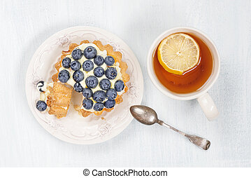 Cake with blueberries and tea with lemon