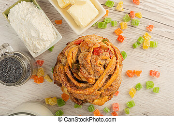 Cake with candied fruits on a wooden background and ingredients
