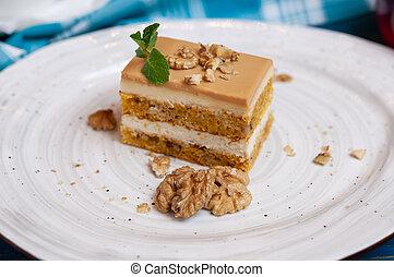 Cake with cream and walnuts on a white plate