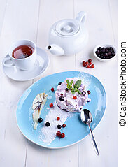 Cake with fresh berries on a blue plate next to a cup of tea and a teapot