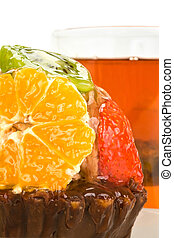 Cake with fruit against a cup of tea