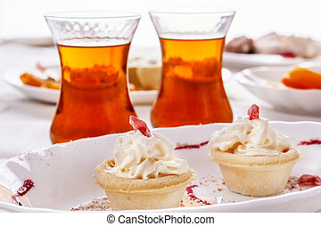 Cake with whipped cream and tea in glass glasses