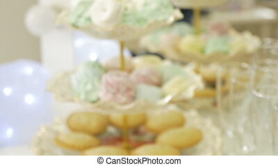 Cakes and biscuits lie on the stand. Moving the camera from...