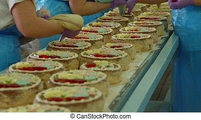 Cakes moving on conveyor belt.