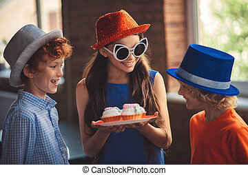 Pretty girl treating friends with delicious cakes