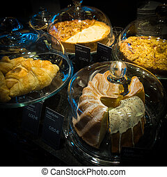 Cakes under bell-glass on display. bakery glass case full of di