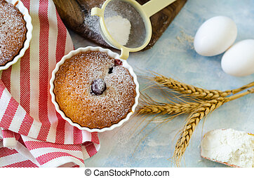 Cakes with cerries on a table in small porcelain cups .There are eggs, flour, wheat, powdered sugar next to cakes.