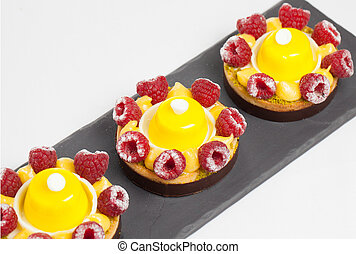 cakes with jelly and raspberry on a black plate