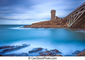 Calafuria Tower landmark on cliff rock, aurelia bridge and sea. Tuscany, Italy. Long exposure photography.