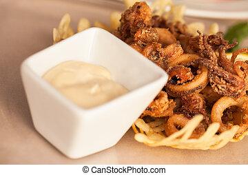 A bowl of calamari with a white sauce.